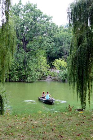 central park: People in boat at Central Park in an autumn cloudy day