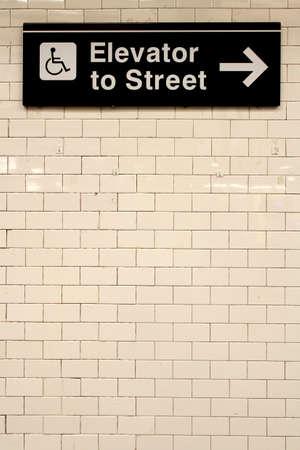 ニューヨーク市の駅地下鉄方向サインオン タイル壁。NYC の地下鉄は 468 局と、世界で最も古く、最も広範な公共交通機関システムの 1 つです。