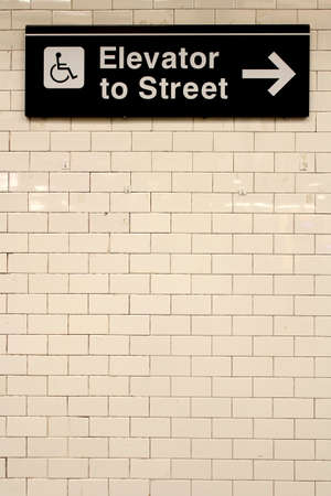 New York City Station subway directional sign on tile wall. The NYC Subway is one of the oldest and most extensive public transportation systems in the world, with 468 stations.