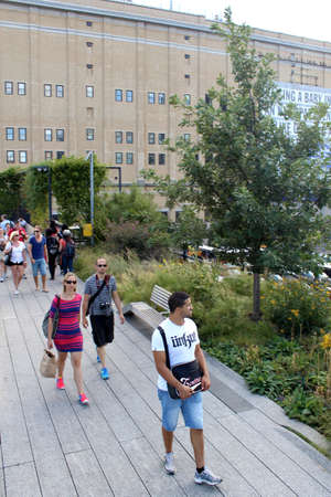 manhattan project: NEW YORK CITY - SEPTEMBER 03: People at High Line Park in NYC on September 03th, 2013. The High Line is a public park built on an historic freight rail line elevated above the streets on Manhattan West Side. Editorial