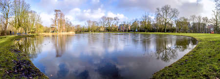 acres: Pond panoramic landscape photo in Vondelpark, Amsterdam. Is a public urban park of 47 hectares (120 acres), opened in 1865 and originally named the \\\Nieuwe Park\\\ and is a favorite place for rest and walking to residents and tourists. Yearly,