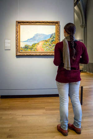 monet: AMSTERDAM, NETHERLANDS - FEBRUARY 08: Visitor at Rijksmuseum admiring La Corniche near Monaco, by Claude Monet, on February 08, 2015 in Amsterdam. The Rijksmuseum is located at the Museum Square, and first opened its doors in 1885. Editorial