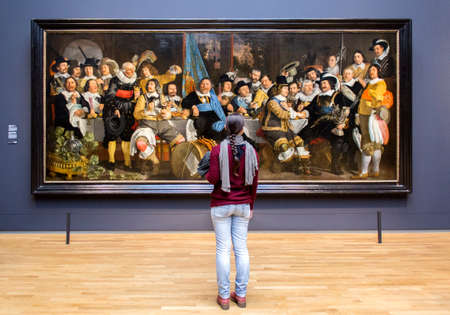 rembrandt: AMSTERDAM, NETHERLANDS - FEBRUARY 08: Visitor at Rijksmuseum admiring Banquet at the Crossbowmen?s Guild in Celebration of the Treaty of M?nster, by Bartholomeus van der Helst, on February 08, 2015 in Amsterdam. The Rijksmuseum is located at the Museum Sq Editorial