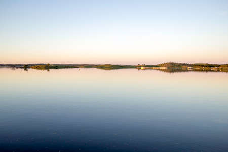 constitutes: Alqueva Dam lake. It impounds the River Guadiana, on the border of Beja and Evora Districts in south of Portugal and constitutes one of the largest dams and artificial lakes (250 km�) in Western Europe. Stock Photo