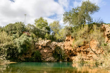 inferno: Beautiful waterfall with small lake in famous hidenn natural picnic rea called Pego do inferno Hells Pond near Tavira Algarve. Portugal.