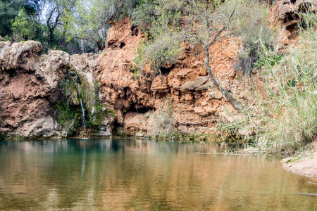 rea: Beautiful waterfall with small lake in famous hidenn natural picnic rea called Pego do inferno Hells Pond near Tavira Algarve. Portugal.