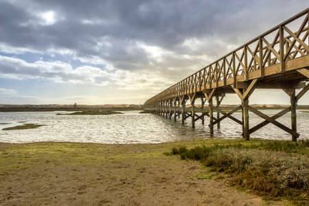 quinta: Landmark footbridge heading to famous Quinta do Lago beach in Ria Formosa wetlands natural conservation region landscape Algarve. Portugal Stock Photo