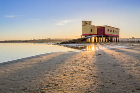 ria: Sunset and historic lifeguard building in the foreground at Fuseta fishing town Ria Formosa conservation park Algarve. Portugal
