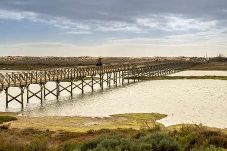 region of algarve: Landmark footbridge heading to famous Quinta do Lago beach in Ria Formosa wetlands natural conservation region landscape Algarve. Portugal Stock Photo