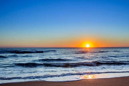 Sunset at Dunas Douradas beach seascape famous destination in Algarve Portugal. Foto de archivo