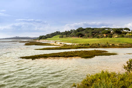 ria: Algarve golf course seascape scenery at Ria Formosa wetlands reserve famous golf and nature destination southern Portugal.