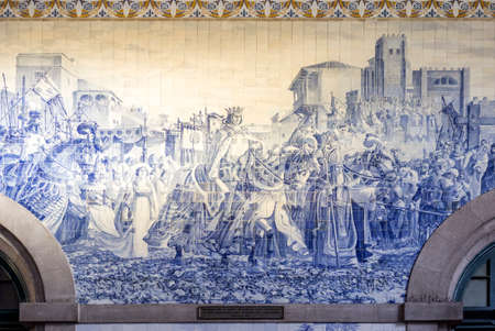 PORTO, PORTUGAL - JULY 04, 2015: Ancient vintage Azulejos panel on inside walls of main hall of Sao Bento Railway Station in Porto city. Tiles Installed between 1905 and 1906 by artist Jorge Colaco. The building station is a popular tourist attraction. On