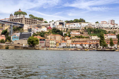Panoramic from Douro river tour boat, view of Dom Luiz Bridge and Gaia riverbank, Porto cityscape, Portugal.