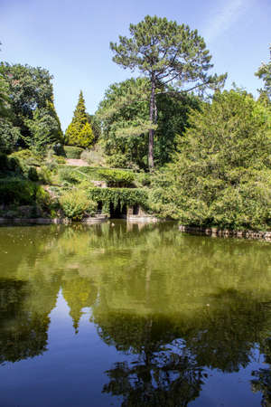 alongside: PORTO, PORTUGAL - JULY 05, 2015: Serralves gardens, a green park that extends over 18 hectares involving the Museum of Contemporary Art Serralves Foundation. Throughout the park works of contemporary art are exhibited alongside the typical flora of the no