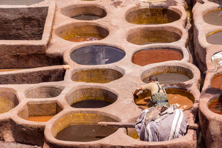 fes: Fes el Bali worker the dye pots at leather traditional tanneries in the ancient medina, in Fez, Morocco.