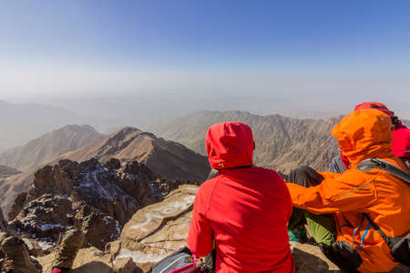 Toubkal national park, the peak whit 4,167m is the highest in the Atlas mountains and North Africa, trekkers relaxing and appreciating view. Morocco Stock Photo