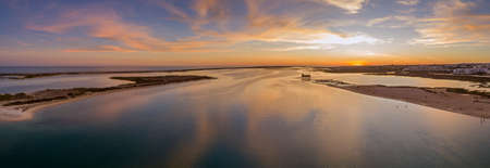 formosa: Aerial sunset panoramic and historic life-guard building at Fuseta fishing town, in Ria Formosa wetlands nature conservation park, Algarve. Portugal.