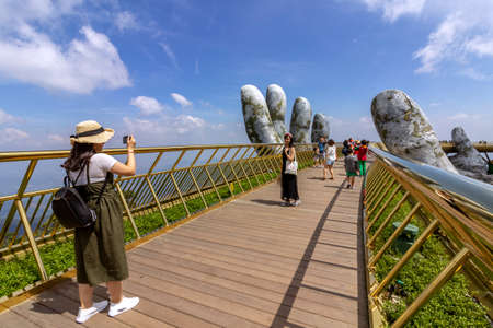 "Da Nang, Vietnam - October 31, 2018: Tourists in Golden Bridge known as ""Hands of God"", a pedestrian footpath lifted by two giant hands, open in July 2018 at Ba Na Hills in Da Nang, Vietnam."