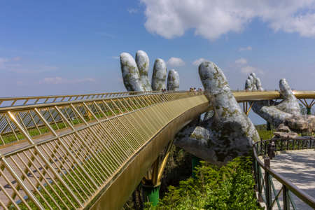 "Da Nang, Vietnam - October 31, 2018: Tourists in Golden Bridge known as ""Hands of God�, a pedestrian footpath lifted by two giant hands, open in July 2018 at Ba Na Hills in Da Nang, Vietnam."