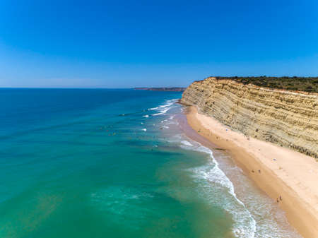 Aerial seascape, of Praia Porto de Mos (Beach and seaside cliff formations along coastline of Lagos city), famous destination in Algarve. South Portugal. Imagens
