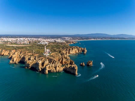 Aerial Scenic seascape, of Ponta da Piedade promontory (cliff formations along coastline of Lagos city), famous natural landmark destination, Algarve. South Portugal.