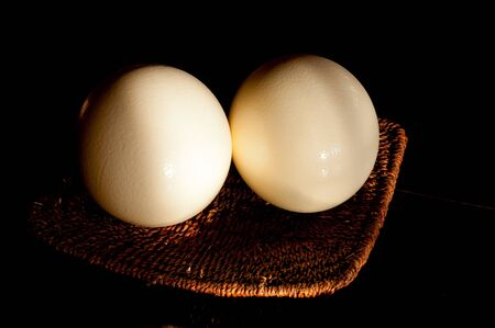 Two ostrich eggs on a wicker basket illuminated by natural light from a window