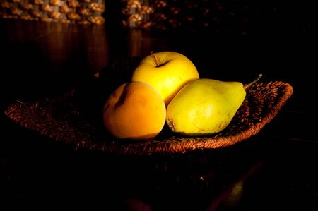 Three pieces of fruit arranged on a dark background and illuminated by natural light coming through the window