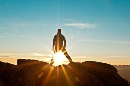 bewonderen: Jonge man die op de top van een berg met uitzicht op een stralende dageraad Stockfoto