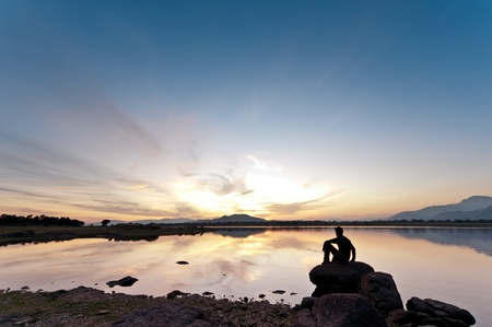 Young man sitting on a rock watching a gorgeous sunset on the lake