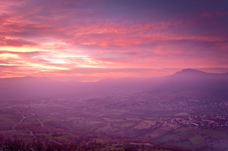 Seen from the viewpoint of a mountain landscape of a village in a valley in a stunning colorful sunset. Stock Photo