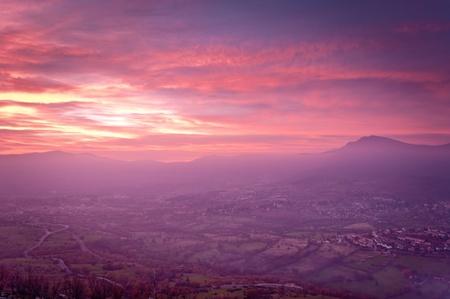 paysagiste: Vu du point de vue d'un paysage de montagne d'un village dans une vallée dans un magnifique coucher de soleil coloré.