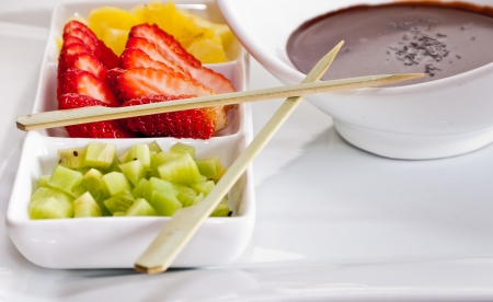 Cut fruit and molten chocolate ready to prepare a few delicious sweet skewers photo