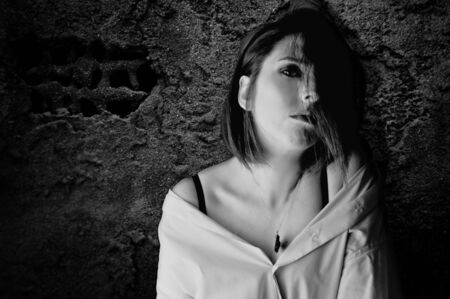 black and white portrait of beautiful woman with serious and pensive face in a dark and gloomy Stock Photo - 15880522
