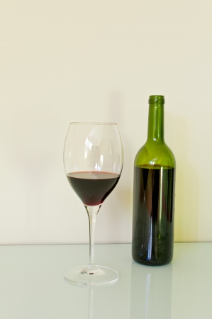 Glass and bottle of red wine with a white background photo