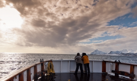 Two men in the prow of the ship sailing in the Norwegian fiords  Stock Photo
