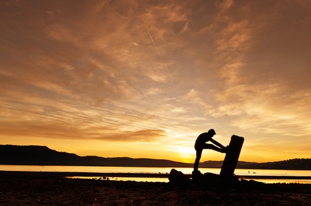 Man doing stretchings at the sunset in a trunk close to the lake in an idyllic landscape of mountain photo