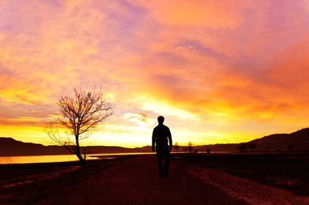 Man walking at sunset on the mountain lake in a majestic summer sunset Stock Photo - 16696445