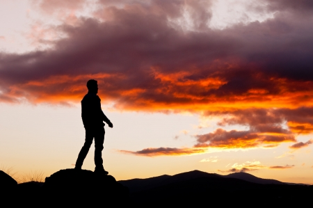 Man s silhouette in the high of a hill in a spectacular sunset Stock Photo