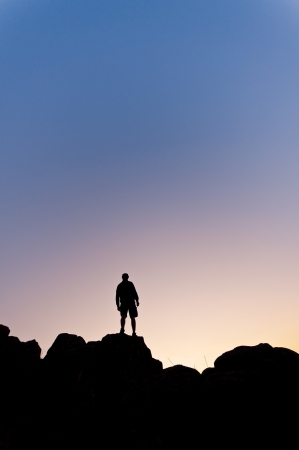 Man s silhouette in the high of a hill at the sunset - Vertical