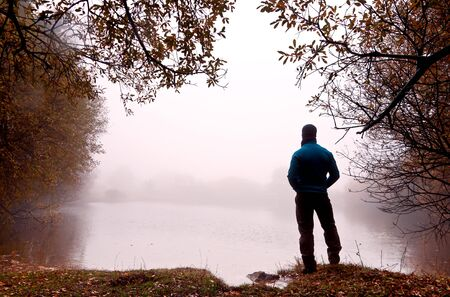 Man in foot to the shore of a lake covered by a dense fog Stock Photo - 16752074