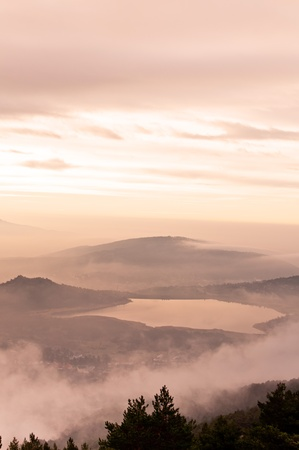 Dawn dress from the top of a mountain with a thick low fog that the people covers - Vertical photo