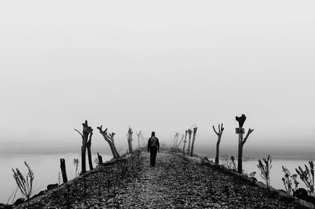 hombre solitario: Hombre caminando en una niebla espesa en salvaje paisaje desolado Negro y blanco