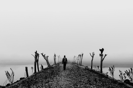 alone in the dark: Man walking in a thick fog on wild desolate landscape  Black and white  Stock Photo