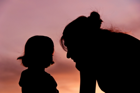 Silhouettes at sunset of a mother and her daughter showing her affection and tenderness  5 Stock Photo - 17490649