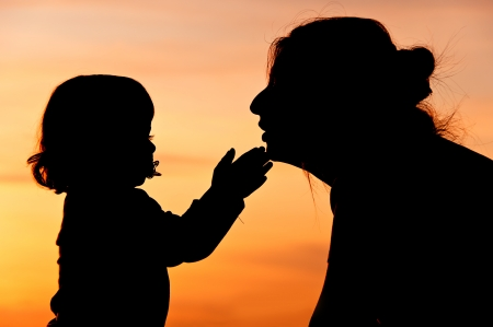 Silhouettes at sunset of a mother and her daughter showing her affection and tenderness - Horizontal  4 Stock Photo - 17490645