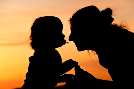 caresses: Silhouettes at sunset of a mother and her daughter showing her affection and tenderness - Horizontal  3 Stock Photo