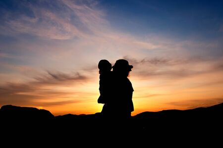 Silhouettes at sunset of a mother and her daughter showing her affection and tenderness - Horizontal  2 Stock Photo - 17490651