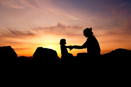 Silhouettes at sunset of a mother and her daughter showing her affection and tenderness - Horizontal Stock Photo