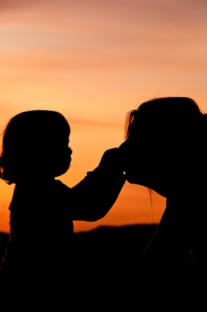 Silhouettes at sunset of a mother and her daughter showing her affection and tenderness - Vertical  2 Stock Photo - 17490644