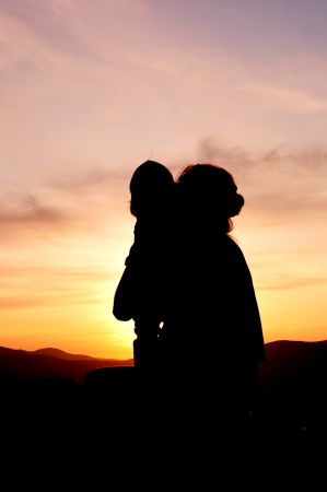 Silhouettes at sunset of a mother and her daughter showing her affection and tenderness - Vertical Stock Photo - 17490642